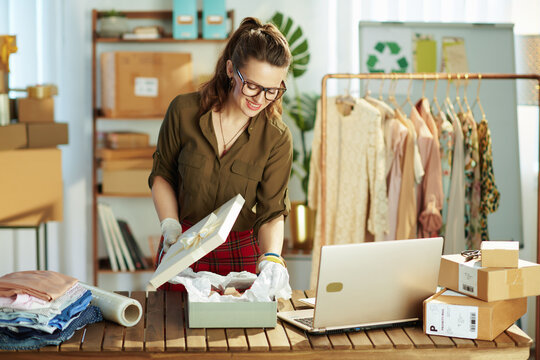 business owner woman using laptop and packing product