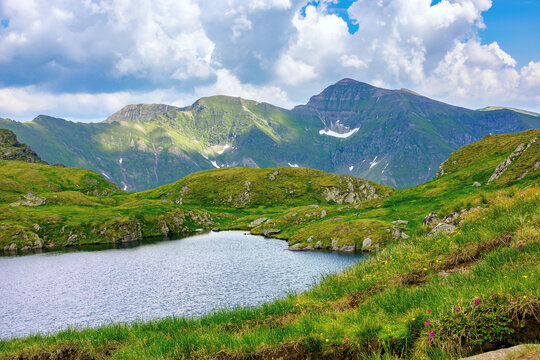 summer scenery with lake on high altitude. beautiful landscape of fagaras mountain ridge in summer. open view in to the distant peak beneath a fluffy clouds