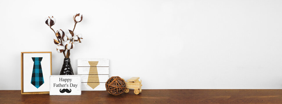 Fathers Day decor with rustic wood signs and cotton branches on a wood shelf against a white wall banner background. Copy space.