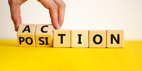 Action or position symbol. Businessman turns wooden cubes and changes the word position to action. Beautiful yellow table, white background, copy space. Business and action or position concept.