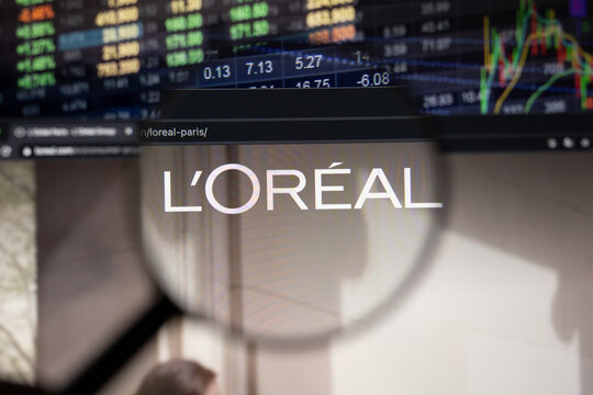 L'oreal company logo on a website with blurry stock market developments in the background, seen on a computer screen through a magnifying glass