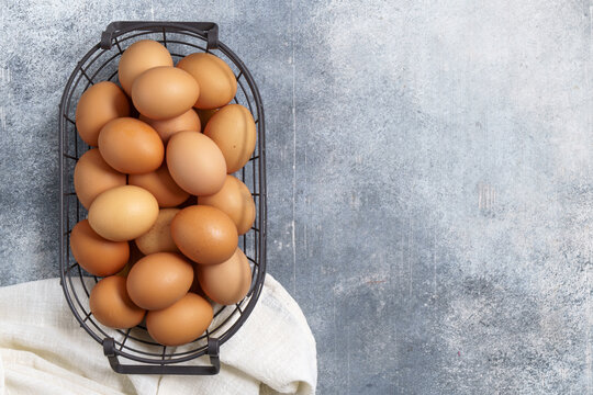 Eggs in wire basket on rustic table with copy space, top view