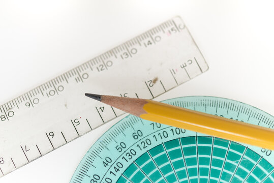 detail of an old, well used aqua green protractor, clear plastic ruler, and pencil on white