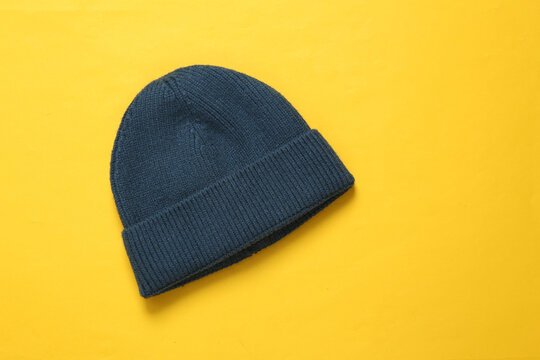 Beanie hat on yellow background. Top view