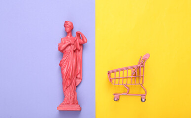 Creative layout. Pink Antique greek goddess statue with shupermarket trolley on purple yellow...