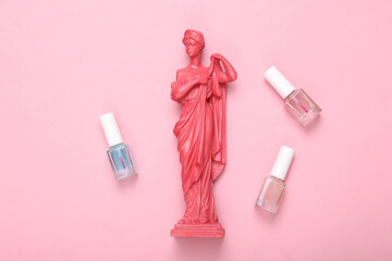 Creative beauty layout. Pink Antique greek goddess statue and bottles of nail polishes on pink...