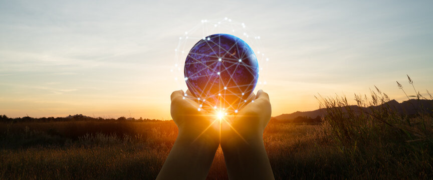 5g and futuristic technology concept.Silhouette a woman use hand holding world,social media networking,cryptocurrency,IoT and blockchain on sunset backgrounds.Elements of this image furnished by NASA