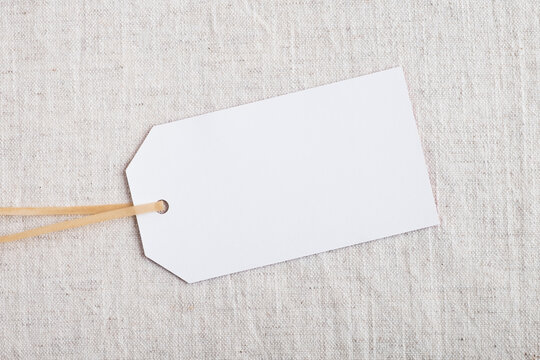 Empty tag card or label mockup for design on pastel natural linen fabric. Branding, sale and shopping concept. Top view, flat lay, copy space