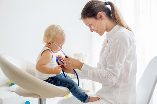 Pediatrician examining baby boy. Doctor using stethoscope to listen to kid