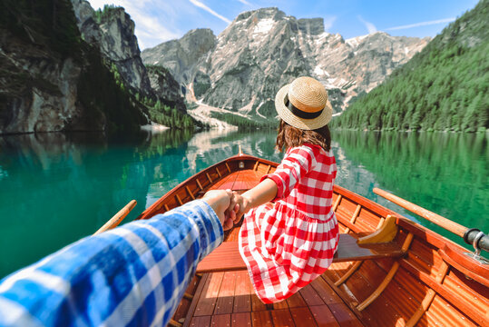 follow me concept. couple holding hands at wooden boat at mountain lake