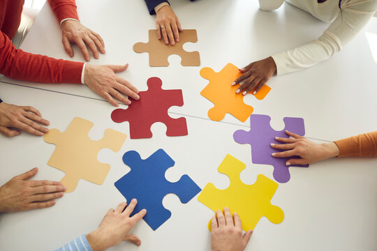 Business team looking for solution to problem. Diverse people join colorful puzzle parts as symbol of teamwork. Group of workers put colorful jigsaw pieces together as metaphor for creative search