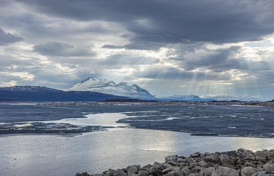 Spring landscape with the half frozen reservoir Akkajaure and the mountain range of Akka in Sarek National Park under overcast sky with sunbeams, Lapland, Sweden.
