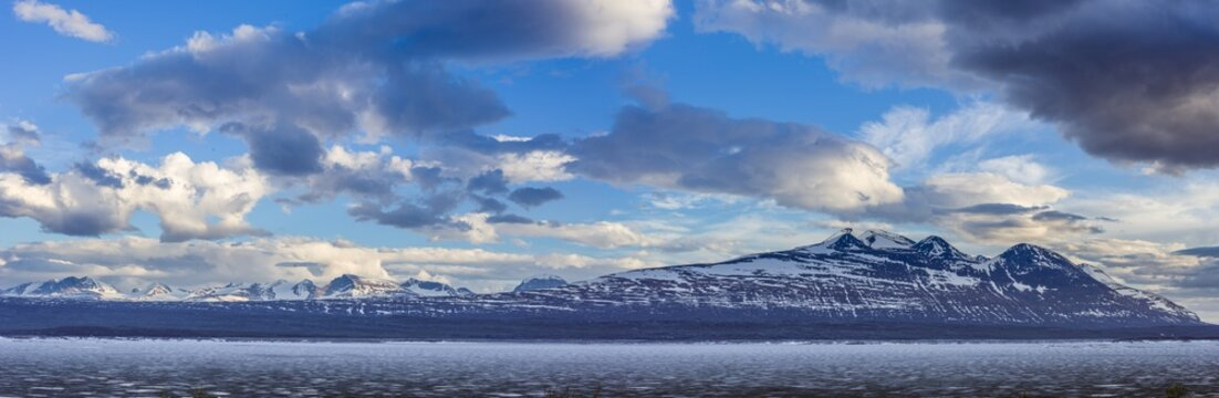 Panoramic image of a landscape in spring with the frozen reservoir Akkajaure and the Akka mountain range in Sarek National Park, Lapland, Sweden.