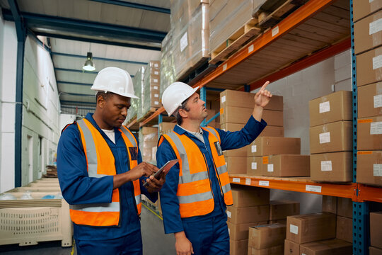 Two multiracial male workers working together in a manufacturing plant