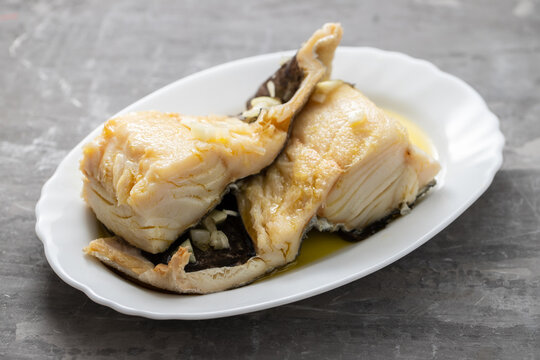 boiled cod fish with olive oil on white dish