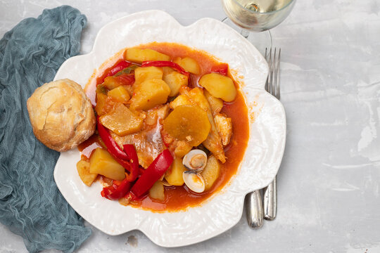 portuguese fish stew with bread in white dish and glass of wine