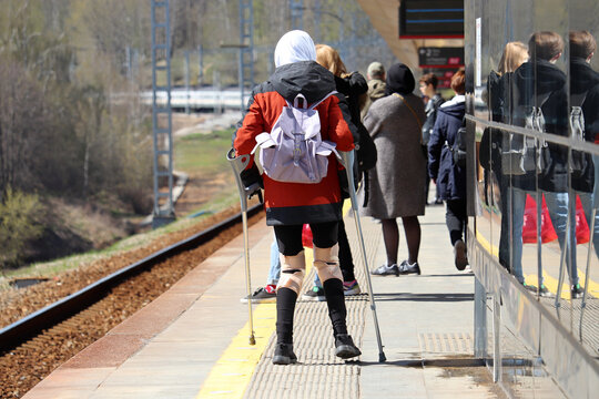 Orthosis for legs, woman with crutches standing on railway station in crowd op people. Orthopedic devices for immobilizing knees, treatment of injured, broken or sprain legs