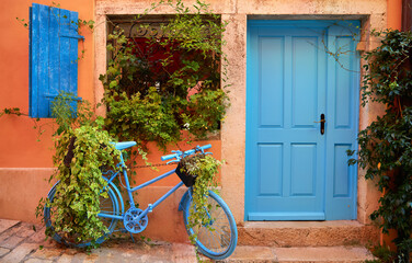 Rovinj, Istria, Croatia. Old blue bicycle at street near door of entrance in house among green bushes and flowerpots with flowers. Picturesque cosy lane. Window shutters on windows.