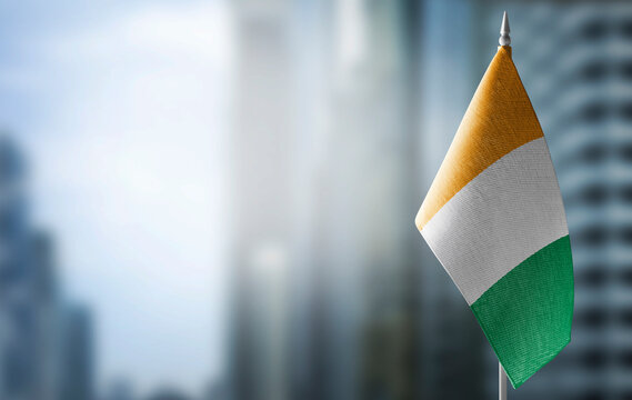 A small flag of Cote dIvoire on the background of a blurred background
