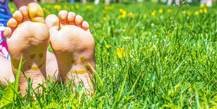 Children's feet with a pattern of paints smile on the green grass. Selective focus.