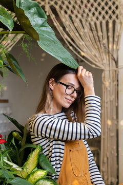 Gardening for stress relief: young female florist enjoy spending time on plants care. Relaxed girl, businesswoman, freelancer or entrepreneur relaxing in home garden after remote work or day in office