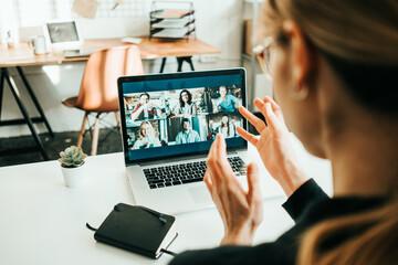 Fototapeta Woman has video call with her remote teammates using laptop.  White loft workspace obraz