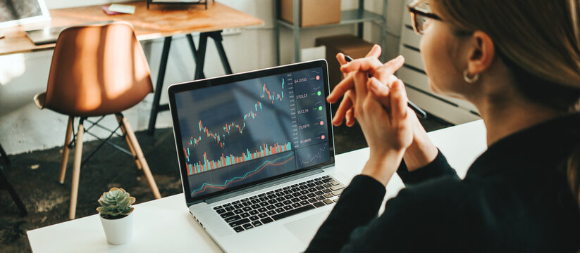 Woman working alone with stock market using laptop, analyzing trading data
