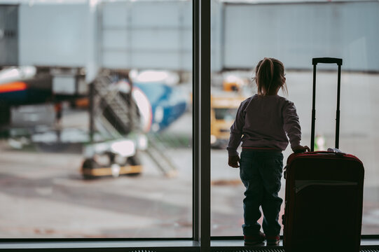 Toddler girl at airport in face mask holding a carry-on luggage