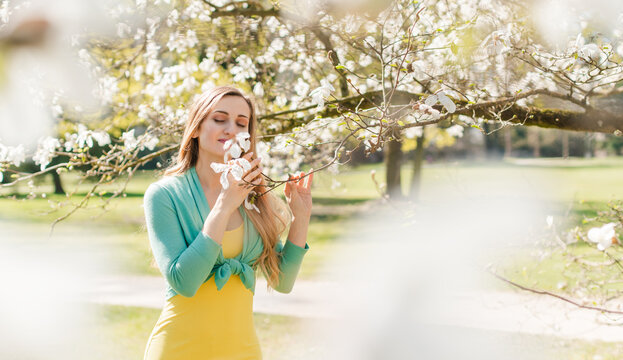 Beautiful woman enjoying the spring blossom in a park