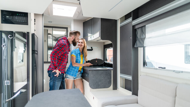 Woman and man testing interior of camper they want to buy or rent
