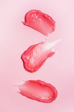 Cosmetic smears on bright Pink background. Lipstick or lip gloss swatch macro wallpaper. Beauty banner