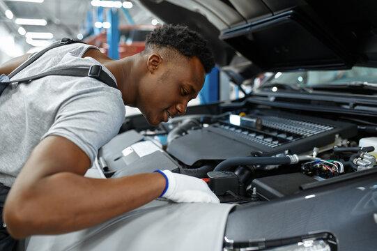 Male mechanic checks engine, car service