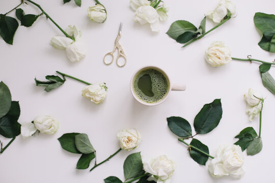 A cup of matcha tea and roses on white background. Flatlay, top view