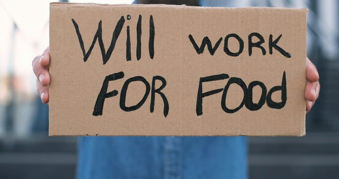 Close up of carton poster with words Will work for food in male hands outdoor. Caucasian workless man holding table with unemployment slogan.
