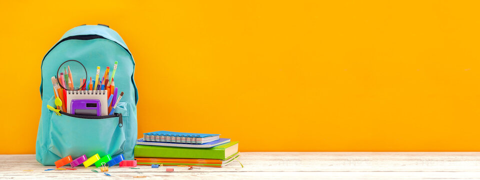 Banner. Concept back to school. Full turquoise School Backpack with stationery on table.