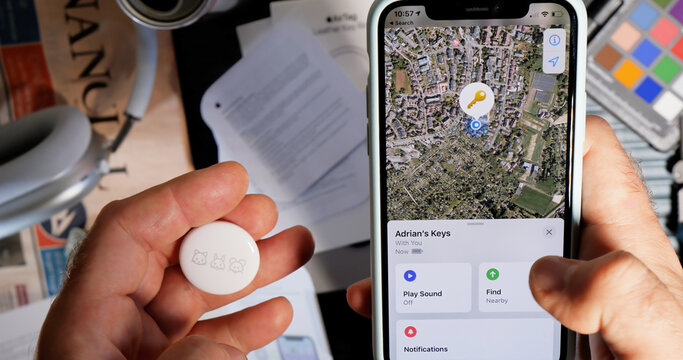 Paris, France - May 2, 2021: Man pov setting up AirTag setup on the iPhone - small device helps people keep track of belongings, using Apple Find My network to locate lost items like keys, wallet, bag