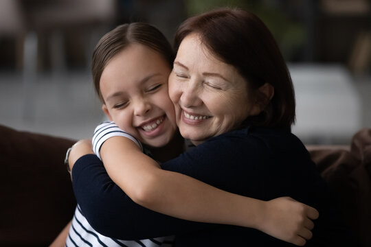 Loving mature grandmother and small teenage granddaughter hug cuddle show care and support in relations. Cute little teen girl child embrace elderly granny feel grateful thankful to grandparent.