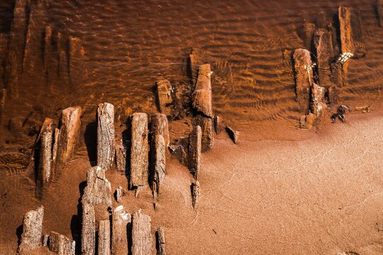 Abstract background with water and a line of the coast with old wooden planks covered with sand. Flat lay