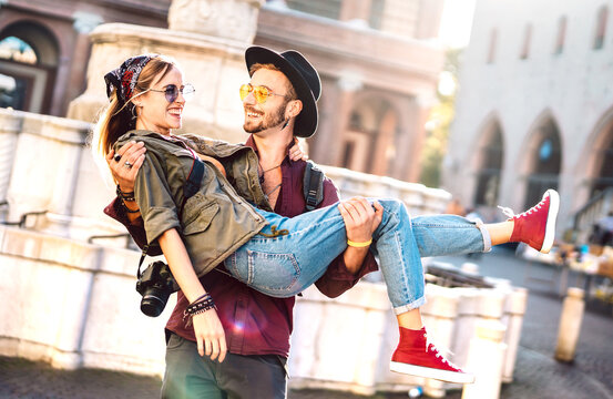 Hipster couple in love having genuine fun wandering at city center - Wanderlust life style and travel vacation concept with guy and girl at old town tour on warm sunshine with bright vivid filter
