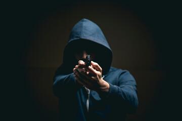 holding a gun on a dark background - fototapety na wymiar