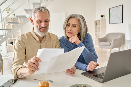 Middle aged senior old couple holding documents reading paper bills paying bank loan online, calculating pension fees, payments, taxes, planning family retirement money finances using laptop at home.