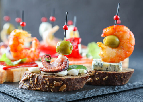 Creative Spanish tapas and seafood sandwich with octopus, olive on a slice of sesame bread with basil leaf and cream cheese for a healthy diet