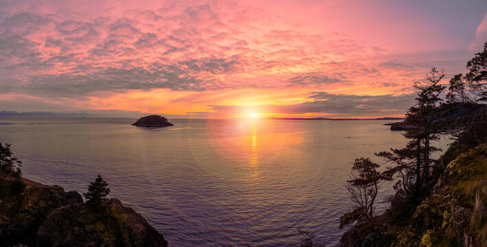 A beautiful pink panorama sunset over the ocean with lens flare and an island and mountains in the distance.