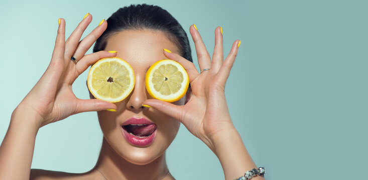Beautiful healthy girl with slices of lemon citrus fruit, food, cosmetics. Healthy eating, diet. Beauty young fashion woman plays with lemons, organic vegetables. Vegetarian concept.