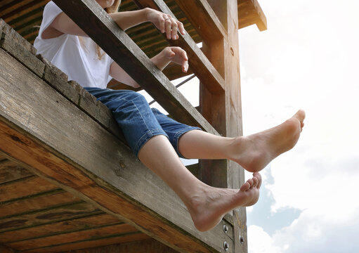 Barefoot woman sitting on wooden dock. Relief for tired legs. Varicose veins prevention concept
