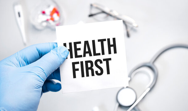 The doctor's blue - gloved hands show the word HEALTH FIRST - . a gloved hand on a white background. Medical concept. the medicine