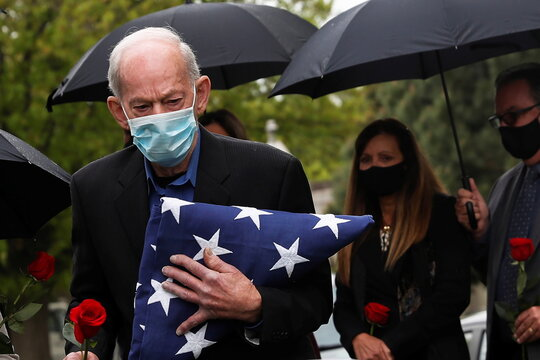 Ben Cancemi wearing a protective mask holds a U.S. flag for his brother Robert, who served in the U.S. Navy, at the Holy Cross cemetery in the Brooklyn borough of New York City