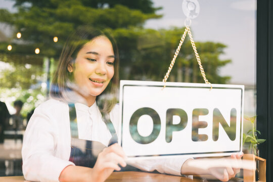 Young asian girl Flip the open label to welcome customer and open the coffee shop in morning. Female asian Barista open the coffee cafe at doorway with reflection in mirror.