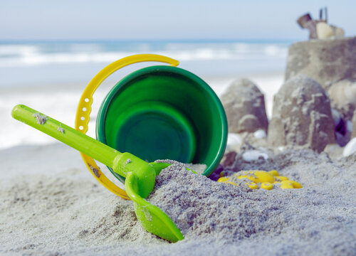 Bucket and spade in the sand next to sandcastles