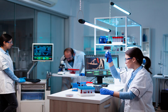 Team of scientific researchers working with professional modern equipment in laboratory. Chemists in pharmaceutical lab examining sample for medical experiment with technology for medicine industry.